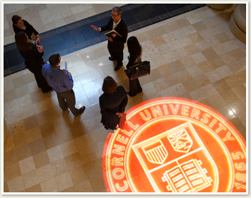 Aerial view of students and teacher standing and talking near Cornell seal on floor