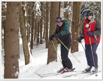 Teacher and student cross country skiing through woods in winter